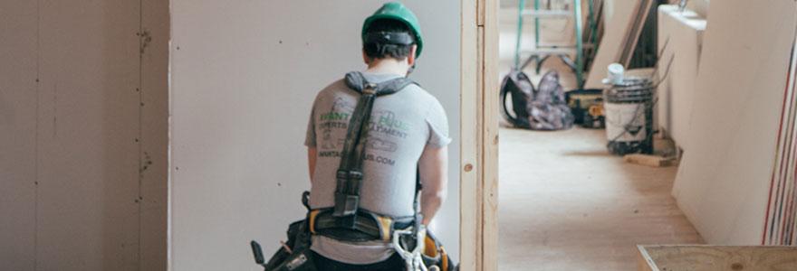 Ouvrier du bâtiment en cours d'installation d'un isolant phonique